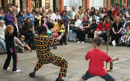 Entertainers teaching people how to limbo dance in Covent Garden