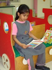 A young girl reads an English language book in a classroom in Dubai